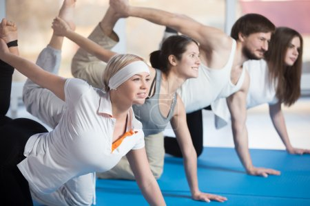 Foto de Fitness, stretching practice, group of four attractive smiling fit young people working out in sports club, doing kneeling kickbacks, exercise for lower back, hips and buttocks in class - Imagen libre de derechos