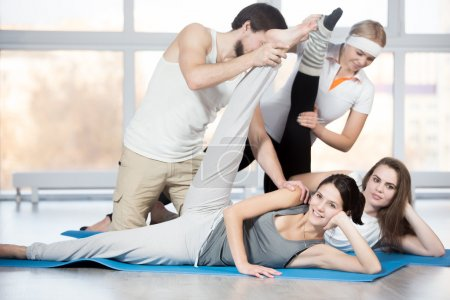 Photo for Fitness, stretching practice, group of four beautiful cheerful fit young people working out in sports club, doing exercises for thighs flexibility on blue mats, partners helping to deepen pose - Royalty Free Image