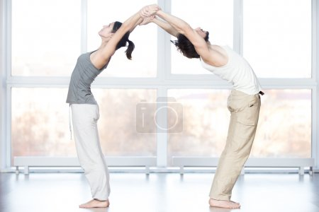 Photo for Fitness practice, group of two beautiful fit young people working out in sports club, doing stretching exercises together in class, Standing Backward Bend posture, Ardha Chakrasana, Half Wheel pose - Royalty Free Image