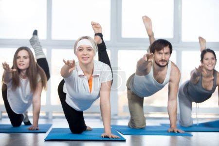 Foto de Fitness, práctica de estiramiento, grupo de cuatro hermosos jóvenes de ajuste feliz que hacen ejercicio en el club deportivo, haciendo contragolpes de rodillas, ejercicio para la parte baja de la espalda, caderas y nalgas con instructor en clase - Imagen libre de derechos