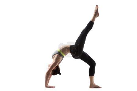 Photo for Sporty beautiful young brunette woman in sportswear bra and black pants working out, One-legged Upward Bow (Wheel) Pose, Eka Pada Urdhva Dhanurasana, studio full length, isolated, white background - Royalty Free Image