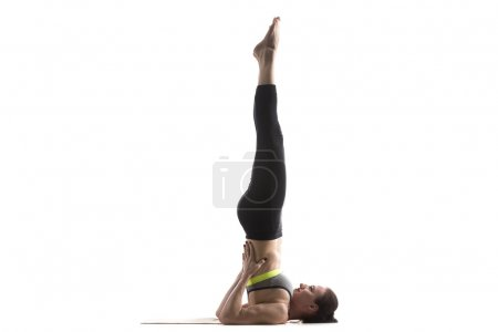 Photo for Sporty fit beautiful young woman in sportswear bra and black pants working out, doing Supported Shoulderstand pose, Salamba Sarvangasana, studio full length, isolated, white background - Royalty Free Image