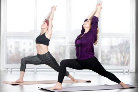 Senior women doing Warrior 1 Pose