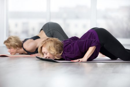 Senior women doing Ashtanga Namaskara pose