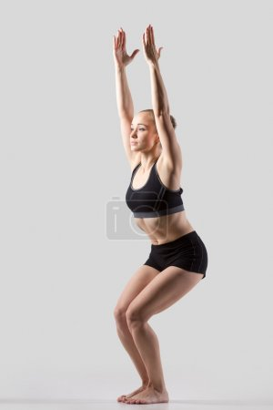 Photo for Sporty beautiful young woman practicing yoga, doing Chair Pose (Fierce, Wild, Awkward posture), Utkatasana, working out wearing black sportswear, studio full length, grey background - Royalty Free Image