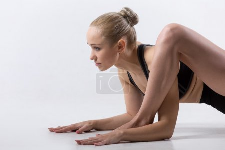 Photo for Portrait of sporty beautiful young woman practicing yoga, doing low lunge exercise, Hip opener Utthan Pristhasana, Lizard Pose (dragon yin posture), working out wearing black sportswear, studio - Royalty Free Image