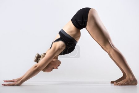 Photo for Sporty beautiful young woman practicing yoga, doing downward facing dog pose, adho mukha svanasana (sun salutation exercise), working out wearing black sportswear, studio, full length, side view - Royalty Free Image