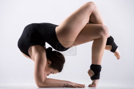 Photo for Beautiful flexible young athlete woman in black leotard working out, doing art gymnastics backbend pose, acrobatic exercise, full length, studio, white background, isolated - Royalty Free Image