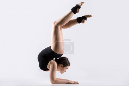 Photo for Beautiful flexible young gymnast athlete woman in black leotard working out, doing acrobatic exercise, handstand with backbend, full length, studio, white background, isolated - Royalty Free Image