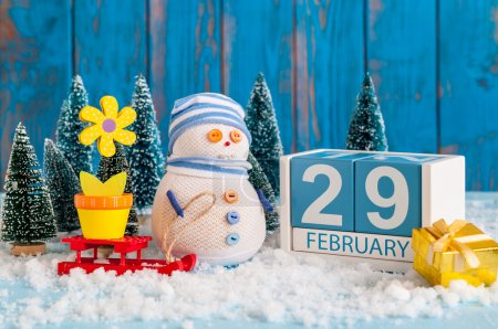 February 29th. Cube calendar for february 29 on wooden surface with snowman, sled, snow, fir and spring flower. Leap year, intercalary day