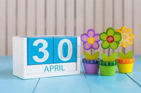 Photo pour Le 30 avril. Image du 30 avril calendrier de couleurs en bois sur fond blanc avec des fleurs. Fin du mois. Jour du printemps, espace vide pour le texte. Journée internationale du jazz . - image libre de droit