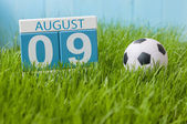 August 9th. Image of august 9 wooden color calendar on green grass lawn background with soccer ball. Summer day. Empty space for text