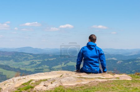 Man, traveler sitting on the edge of a cliff and watching peaceful landscape.