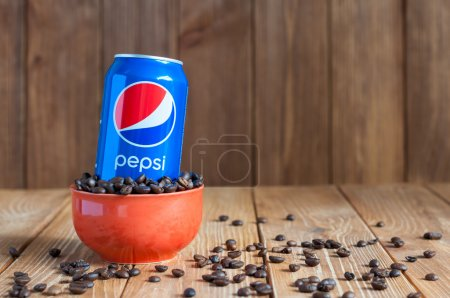 Kiev, Ukraine, April 2015. Can Pepsi cola in a bowl of coffee standing on dark wooden background with empty space. Carbonated soft drink that produced and manufactured by PepsiCo. Created, developed