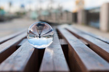 Glass transparent ball on wooden slats background. With empty space