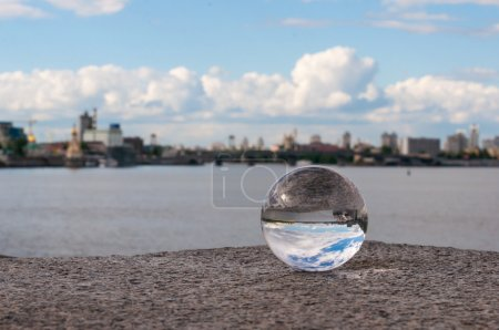 Glass transparent ball on city background and grainy surface. With empty space