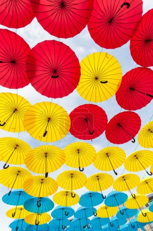 Many open in sky umbrellas  give a guarantee that rain will not spoil the day. Red, yellow and blue umbrella. Kiev, Ukraine.