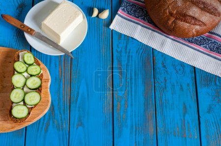 Freshly baked bread, sandwich with sliced cucumbers and butter on dish in rural or rustic kitchen at vintage wood table from above. Empty space for text