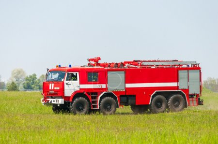 BORYSPIL, UKRAINE - MAY, 20, 2015: Red firetruck Kamaz ride on alarm for instruction for fire suppression and mine victim assistance at Boryspil International Airport, Kiev, Ukraine.