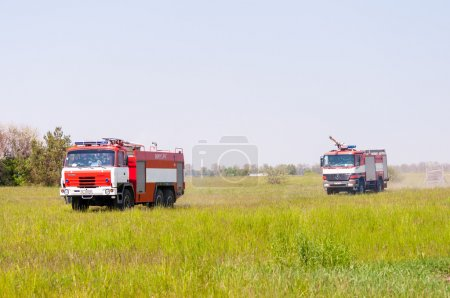 BORYSPIL, UKRAINE - MAY, 20, 2015: Fire-brigade on firetruck Tatra and Mercedes ride on alarm for instruction for fire suppression and mine victim assistance at Boryspil International Airport, Kiev