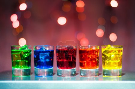 Five shots glasses full of assorted beverages and ice on golden blurred lighting bokeh background