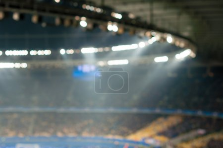 Blurred soccer stadium or ather sport arena at night with projector and stands full of people, fans, crowd