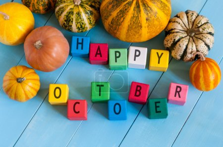 Happy October wooden blocks with many-coloured pumpkins and decor against an old wood background