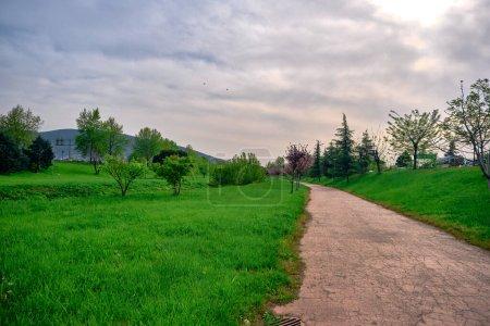 Parc public naturel à Bursa pendant le coucher du soleil avec gravier et sentier pédestre autour de l'herbe verte avec ulu montagne (uludag) arrière-plan dans le centre de la ville.