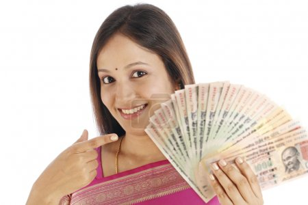 Photo for Happy traditional Indian woman with Indian currency against white - Royalty Free Image