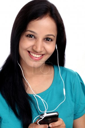 Beautiful young Indian woman listening music