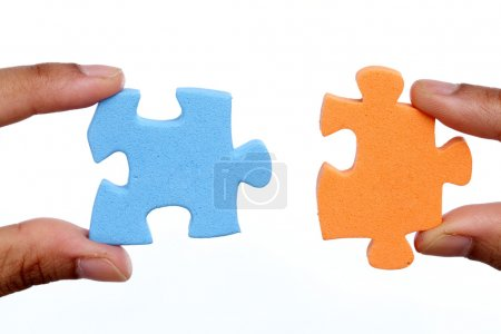 Hands trying to attach two jigsaw puzzle pieces on white background