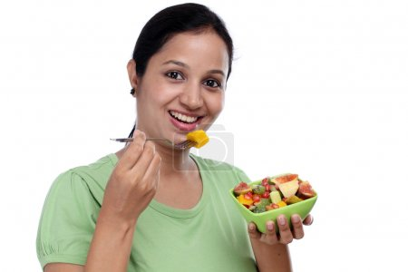 Photo for Young Indian woman eating fruit salad against white background - Royalty Free Image