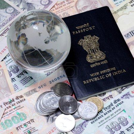 Photo pour Monnaie indienne avec passeport et globe en verre - image libre de droit