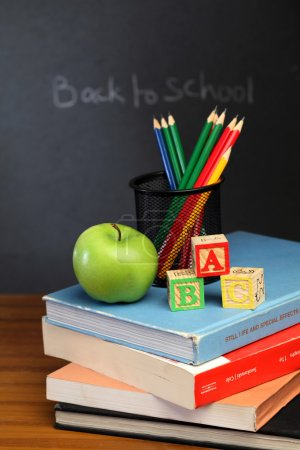 ABC blocks and apple against black board