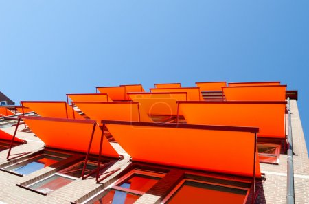 Flats windows with orange shade sail sun protection.