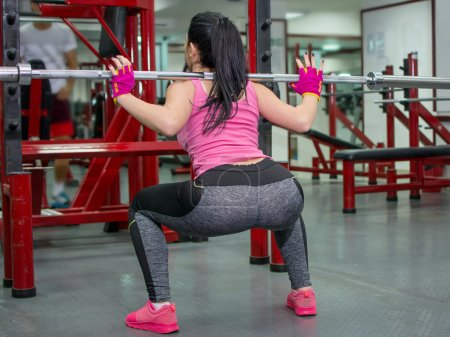 Girl doing squats with a bar