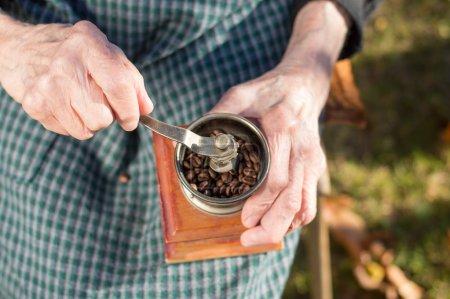 Old woman grinding coffee on a vintage coffee grinder