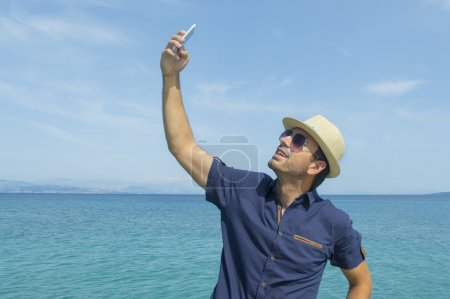 Man taking a selfie with his smart phone on the beach