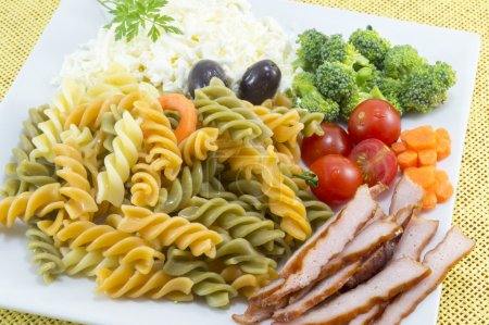 Coloured pasta served with cheese,olives broccoli, cherry tomato