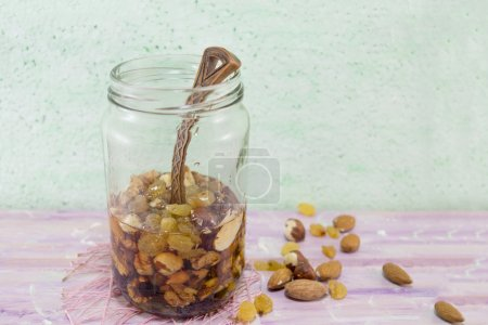 Jar of honey with choped nuts, almond and hazelnuts