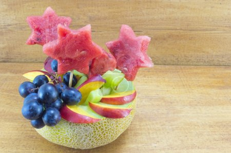 Healthy attractive fruit salad served in a fresh melon on a wood