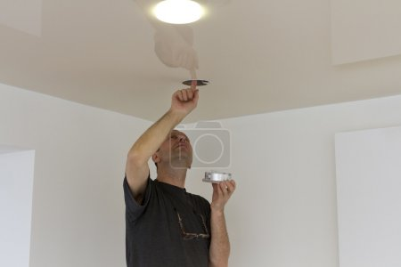 Male hands installing light bulb.