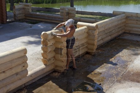 Carpenters lay out of logs wall of a new home.