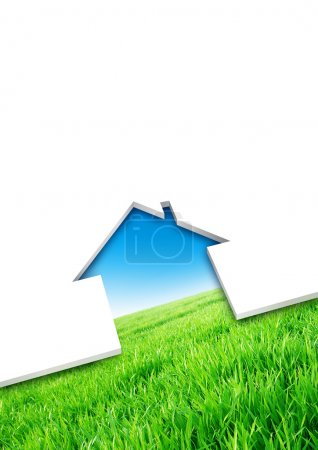Photo for Cutting of a blank sheet, house shaped above a green field background - Royalty Free Image