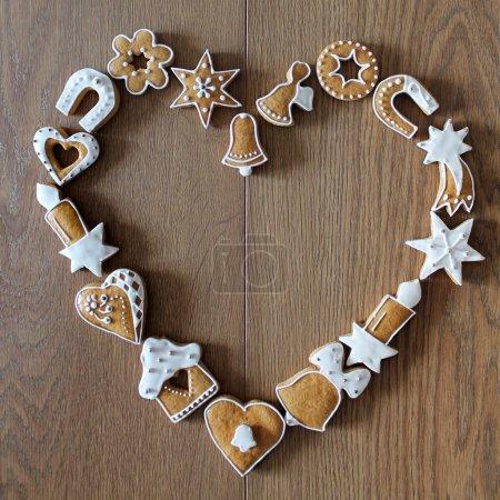 Photo pour Fond de Noël avec les cookies sur la planche de bois (cadre de forme coeur) - image libre de droit