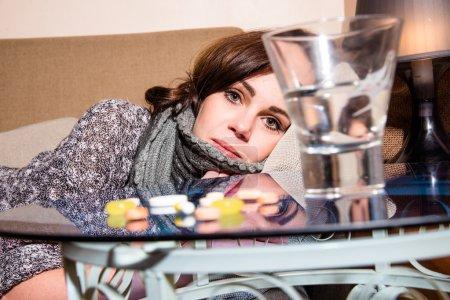 Photo pour Fille malade couché sur le canapé, sur la table sont des comprimés - image libre de droit