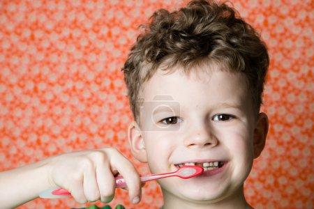 Photo pour Petit garçon brossant les dents avec une brosse à dents - image libre de droit