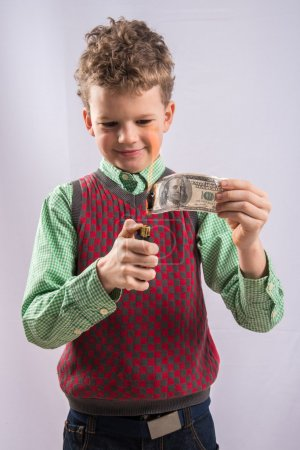 Photo for Boy sets fire to a hundred dollar bill - Royalty Free Image