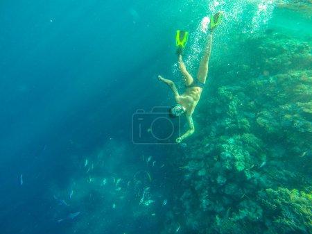 Photo pour Homme nageant sous l'eau sur fond de poissons de mer - image libre de droit