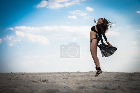 Photo pour Fille en maillot de bain noir sautant sur le fond du désert - image libre de droit